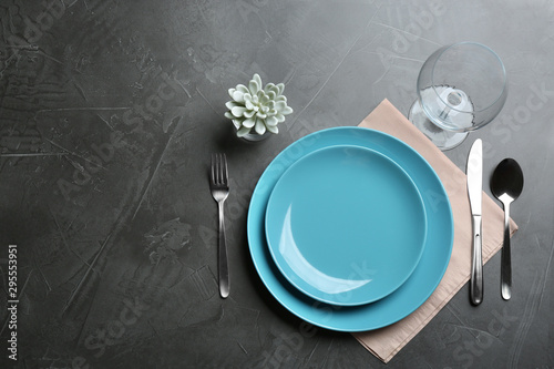 Elegant table setting on grey background, flat lay. Space for text