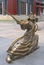 Metal Copper Statue Of Woman Holding Sword Posing Chinese Kung Fu Posture In Ancient Traditional Dress. Dayan Pagoda, Xian China