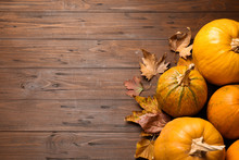 Flat Lay Composition With Different Ripe Pumpkins On Wooden Background, Space For Text. Holiday Decoration