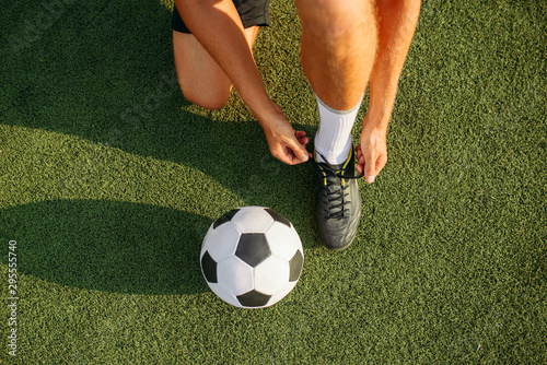 Fotografia, Obraz Male soccer player ties his shoelaces on boots