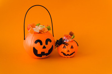 trick or treat for halloween. Pumpkin bucket with sweets and spiders on an orange background. Sweets for kids for Halloween. Copyspace
