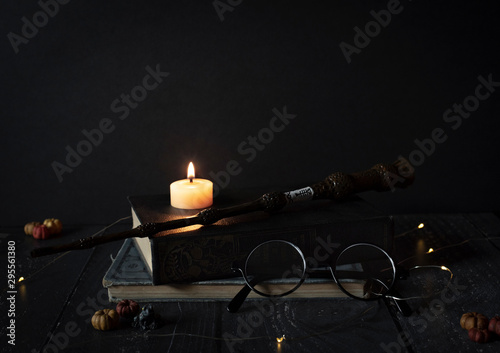 magic wand and spell books on desk with glasses, burning candle, and other witch items, wizards desk, halloween theme, vintage books