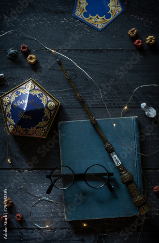 magic wand and spell books on desk with glasses and other witch items, wizards desk, halloween theme, vintage books