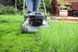 canvas print picture - Clsoeup of a lawnmower cutting tall grass