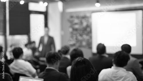 Fényképezés  Speaker on the stage with rear view of audience in the conference hall or seminar meeting, business and education concept