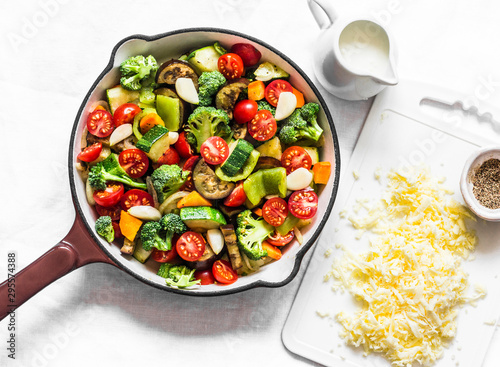 Fototapeta Vegetarian casserole ratatouille, baked in a frying pan on a light background, top view obraz