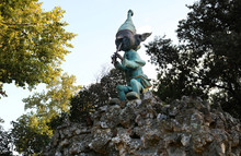 Sculpture Of An Elf Playing A Flute In A Park