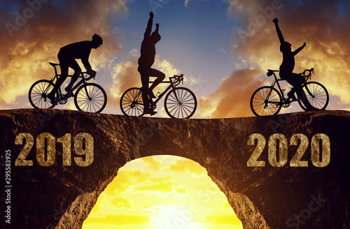 Tela  Three cyclists ride a road bicycle at sunset