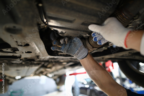 Fényképezés  Focus on hardworking male hands examining modern high-tech automobile underneath pipes in white gloves with precise accuracy