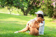 canvas print picture - Asian lifestyle woman playing and hug young golden retriever friendship dog in outdoor the nature park.