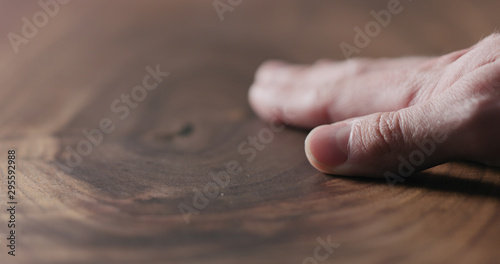 Obraz man hand touch oil finished black walnut wood surface - fototapety do salonu