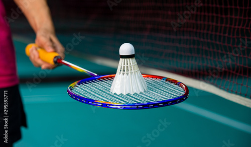 Photo Woman Badminton player holding racket with Badminton shuttlecock on top with blurred net and badminton court background