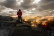 Mann steht auf einen Berg und schaut auf eine brennende Landschaft
