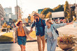 Group of tourists enjoying on vacation, young friends having fun walking on city street during sunset.