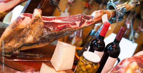 Fototapeta Still life of spanish pork jammon on holder, bottles of wine cheese and olives