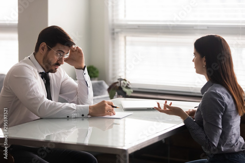 Confused male hr manager listening to female job applicant. Wallpaper Mural