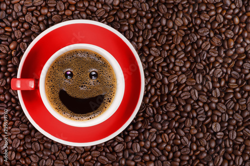 Canvas Prints Cafe coffee background of hot black coffee with smile bubble in red cup on roasted arabica coffee beans background