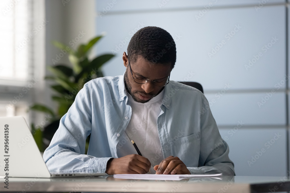 Fototapeta Focused mixed race entrepreneur signing document or contract.