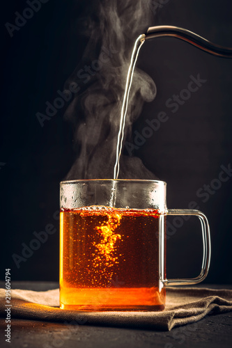 Recess Fitting Tea The process of brewing tea, pouring hot water from the kettle into the Cup, steam coming out of the mug, water droplets on the glass, black background