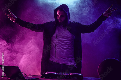 Young stylish man in glasses posing behind mixing console on colored smoke studio background. - 295609344