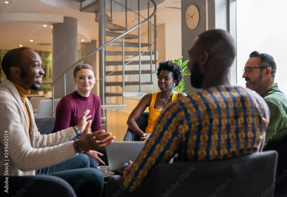 Fototapeta Group of diverse south african business people having a candid meeting in a modern work space