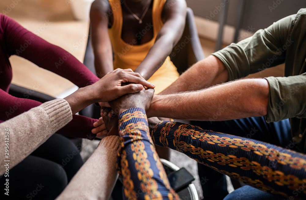 Fototapeta Cropped close of diverse businesspeople putting their hands on top of each other wearing casual clothes and african patterns.