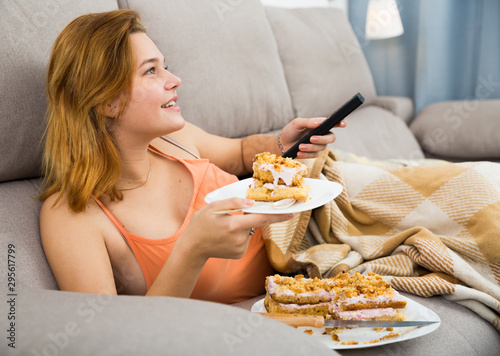 female eating cake at home with tv remote Canvas Print
