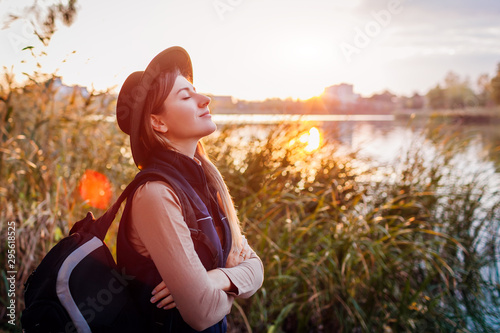 Fototapeta Traveler with backpack relaxing by autumn river at sunset. Young woman breathing deep feeling happy and free obraz