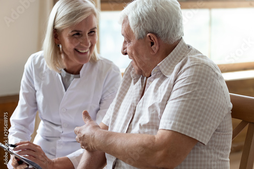 Elderly man patient and middle-aged nurse talking indoors Poster Mural XXL
