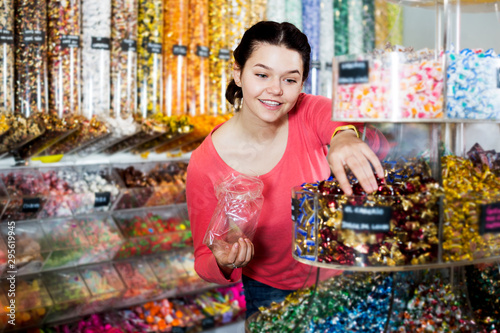 Fotografía Woman posing to photographer picking different candies