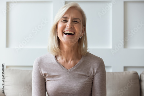 Fotomural  Portrait vivacious elderly woman sit on couch look at camera