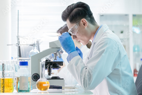 Tuinposter Apotheek Asian scientist use microscope