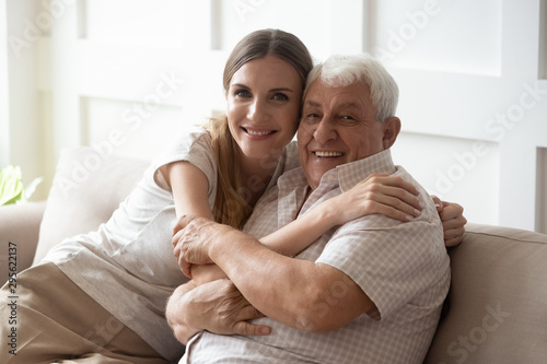 Fotografie, Obraz Adult granddaughter and elderly grandfather embracing sitting on couch indoors