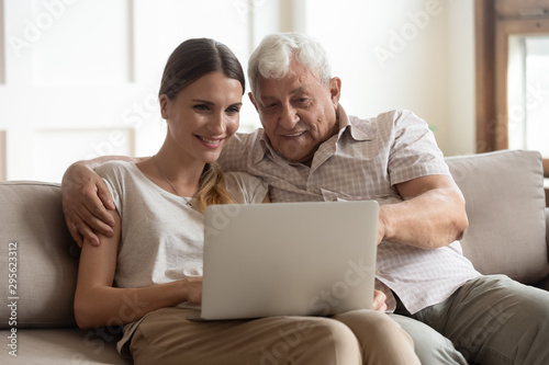 Fotografía  Grandfather and adult granddaughter sitting on couch using laptop