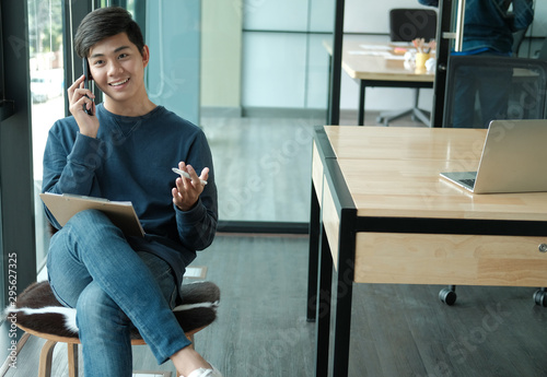 Leinwand Poster  male freelancer talking on mobile smart phone at office