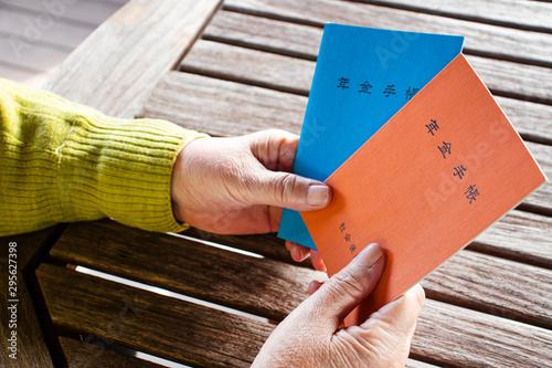 Photo 年金手帳を持つシニア