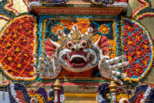 Photo Detail Bade cremation tower with traditional balinese sculptures of demons and flowers on central street in Ubud, Island Bali, Indonesia