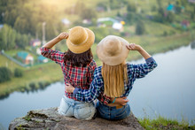 Cheerful Sisters Holding Staw Hats Enjoying Sunset On Top Of A Mountain, Friendsip, Back View Close Up Photo. Relationship, Amazing Landscape And Small Village In The Background Of The Photo