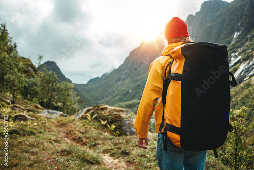 Photo Brave tourist wearing yellow jacket with travel backpack hiking in mountains outdoor journey