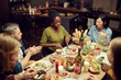 High angle view at multi-ethnic group of people sitting at dinner table together and enjoying delicious food, copy space