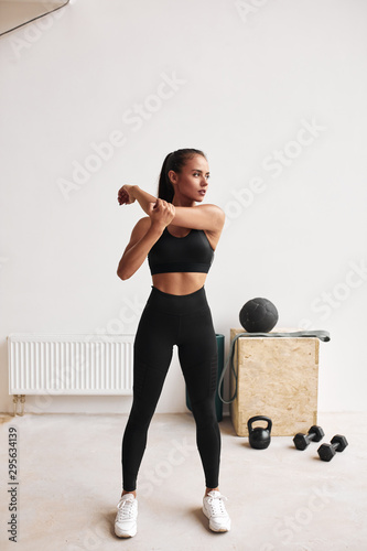 Fotografie, Tablou Slim fitness female in black leggins and topic stretching body, arms