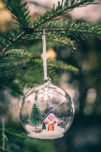 Fotografiet  Transparent cristalball with christmas tree and house inside.