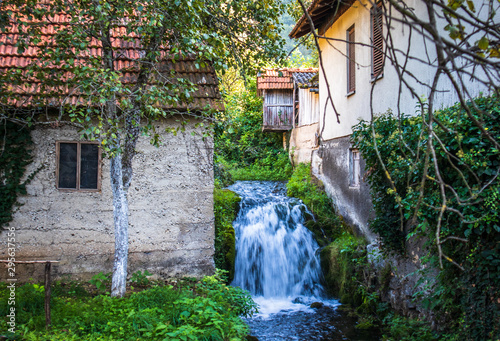 Spoed Fotobehang Bos rivier Small waterfall next to the old house in a yard in village Martin Brod in Bosnia and Herzegovina