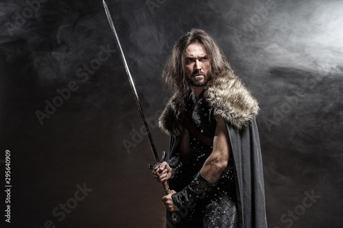 Man dressed in medieval armor and raincoat with longs word fighting against enemy Fototapete