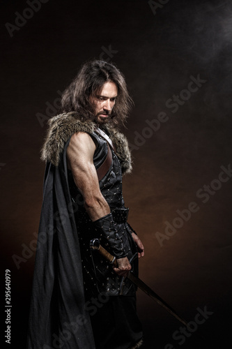 Photo Man dressed in medieval armor and raincoat with longs word fighting against enemy