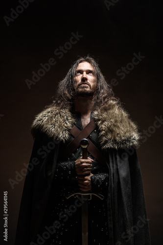 Man dressed in medieval armor and raincoat with longs word fighting against enemy Fototapet
