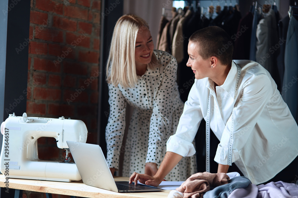 Fototapety, obrazy: Designer in white shirt and model in white dress together in atelier. Look and smile, happy working together, creating new clothing.