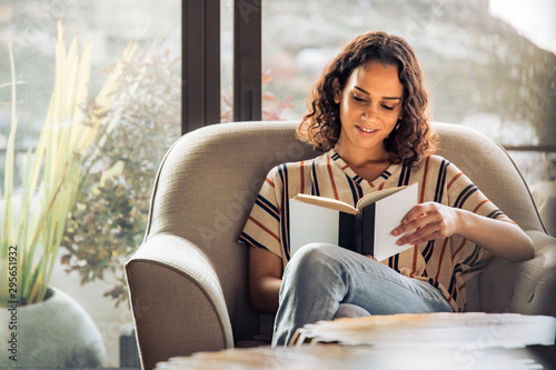 Close up of female sitting on sofa with open book and coffee Canvas