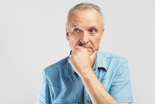 Portrait Of A Stylish Modern Elderly Man On A White Background In The Studio. Senior Boss Thinking In A Pensive Pose