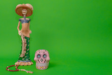 Calavera De La Catrina Statuette, Mexican Symbol Of Day Of The Dead, Next To A Wooden Rosary And A Pink Skull, On A Uniform Green Studio Background